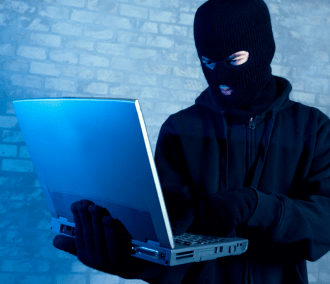 A masked figure using a laptop for hacking