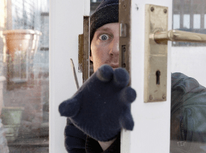 A man attempting home intrusion through the door