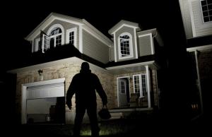 A dark figure robbing an open garage